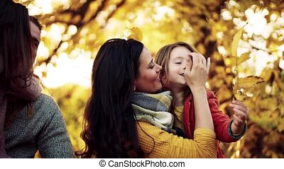 A portrait of young family with two small children in autumn nature.