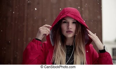 A portrait of young girl or woman with earphones outdoors in winter.