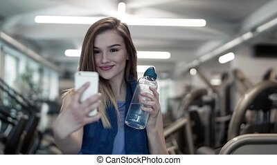 A portrait of young girl or woman with smartphone in a gym,...