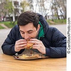 man eating very tasty burger in street food cafe
