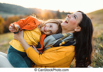 A portrait of young mother with a small daughter in autumn nature at sunset.