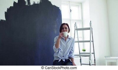 A portrait of young woman painting wall black. A startup of...