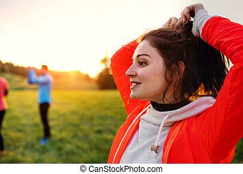 A portrait of young woman with group of people doing exercise in nature.