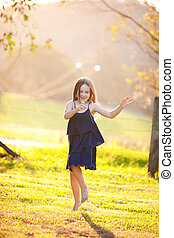 A portriat of a beautiful young girl in the outdoors.