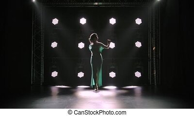 A posh woman in a long sexy dress with a deep slit walks in a dark studio against a background of neon lights. A brunette in high heeled sandals walks straight and looks down. Slow motion