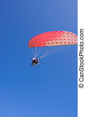 A powered paraglider pilot in flight with a blue sky in the background