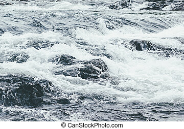 A powerful stream of mountain river. The fast current of water.