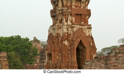 A wide shot with tilting view of the ruins of one of Wat Mahatthat's Prang, focusing on it's eroding stucco and gilded brick structure with similar spire-like towers in the background.
