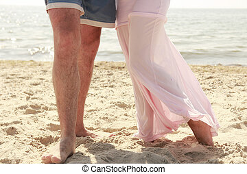 Pregnant couple in love feet on the beach
