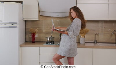 A pregnant girl is cooking in a modern kitchen and is ...