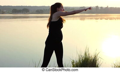 a Pregnant Girl Stands on a Mat, Throws Her Arm Aside, at Sunset .