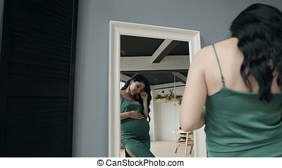 A pregnant woman dressed in a green evening dress is displayed in a mirror.