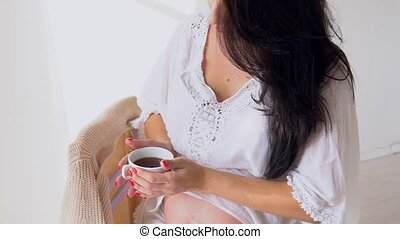 a pregnant woman drinking hot tea in a white kitchen - a...