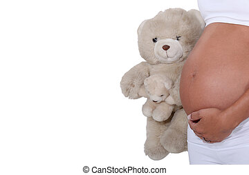 A pregnant woman holding a teddy bear.