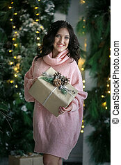 A pregnant woman in a pink sweater holds a paper box with a gift in her hands against the background of a green Christmas tree