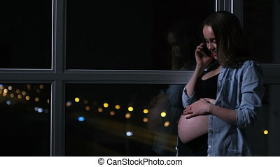 A pregnant woman in the night talking on the mobile phone hands touching the stomach standing at the window