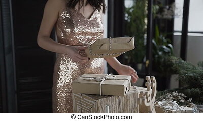A pregnant woman makes boxes in which packed gifts for the family for the New Year's . Conception of pregnancy. New Year. Christmas holidays. Gifts