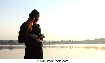 a Pregnant Woman Plays With Slippers For Her Baby at Sunrise in Autumn in 4k