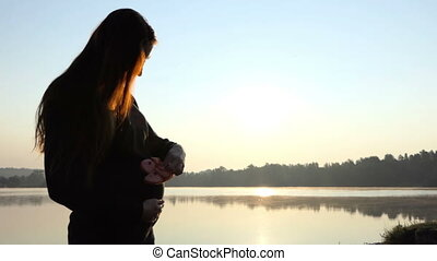a Pregnant Woman Plays With Slippers For Her Baby on a Lake Bank in 4K.