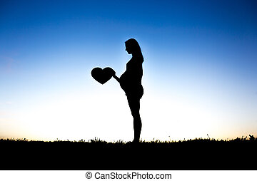 Pregnant woman touch her belly sit on the ground against the light