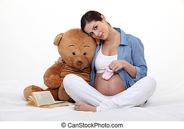 A pregnant woman with a teddy bear.
