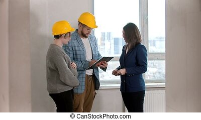 A pregnant woman with her husband signing papers for the apartment rental with a real estate agent
