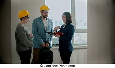 A pregnant woman with her husband talking with a real estate agent in draft apartment