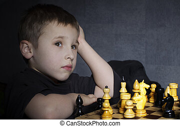 A preschool child plays chess. The little boy is thinking over the move. The course of the horse.
