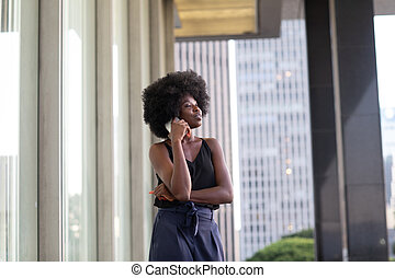 A pretty African american business woman talking on a cell phone at office building in the city