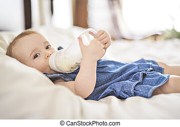 Pretty baby girl drinks water from bottle lying on bed