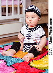 A pretty baby in a striped shirt and hats seated on the mat in the room