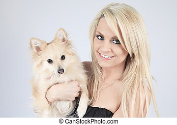 A pretty blond girl sitting with is dog on the sofa
