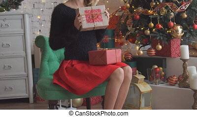 A pretty blond haired woman opens a gift.