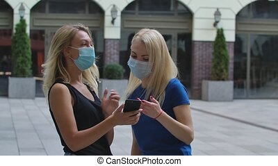 A pretty blonde learns how to get to the right place by showing a smartphone to a woman she meets on the street. Both women wear protective medical masks. Corona virus health protection concept. Slow motion. Close up outdoors on blurred building background.
