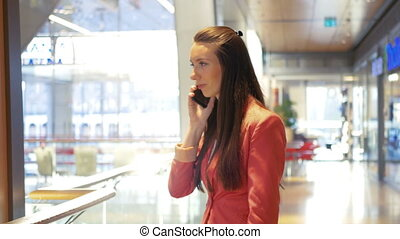 A pretty business lady talks after shopping in a shopping mall on the smartphone and laughs