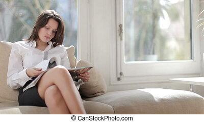 a pretty businesswoman reads, relaxing, or awaiting an interview
