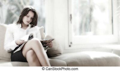a pretty businesswoman reads, relaxing, or awaiting an...
