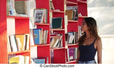A pretty girl on a skateboard pulls up to a bookshelf on the...