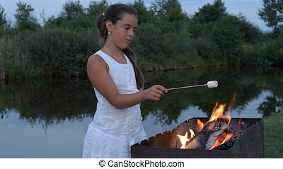 girl fries marshmallows on the fire near the pond