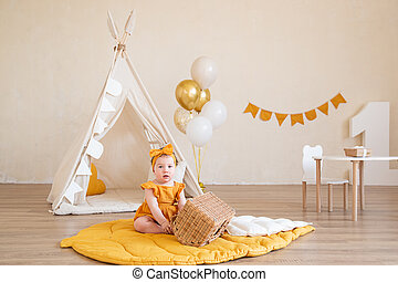 A pretty one-year-old girl in yellow clothes is sitting on the floor