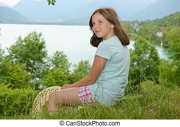 pretty pre teen girl sitting in grass