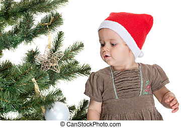 A pretty smiling little girl is decorating a christmas tree; isolated on the white background