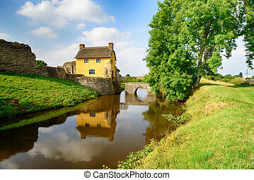 A pretty thatched cottage built in to the ruins of Stogursey Castle in Somerset