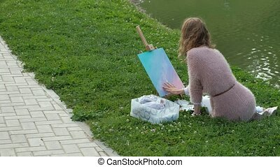 A pretty woman with red hair, paints a picture on canvas, which stands on the easel. The lady is in the open air near the lake of the river, she draws from life