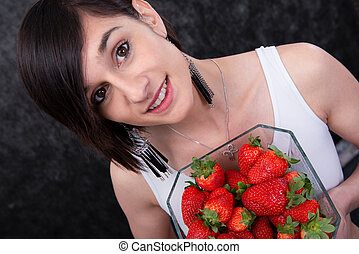 pretty young brunette woman with a bowl of strawberry