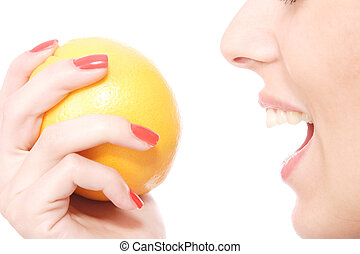 A pretty young woman holding an orange
