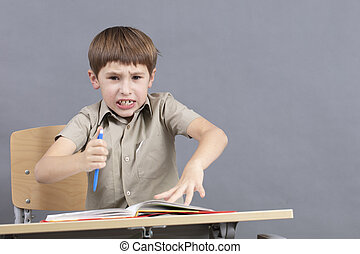 A primary school student is doing homework. The child at the desk with the textbook is angry. The boy does not want to study. A seven-year-old child goes crazy for lessons.