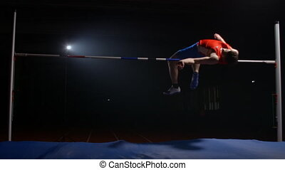 A professional athlete performs a jump over a crossbar and knocked down the bar during a high jump