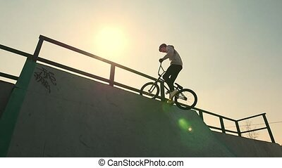 A professional BMX rider in grey hoodie going up on the ramp...