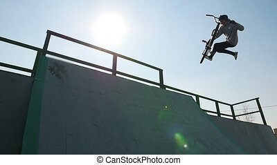A professional BMX rider in grey hoodie performing a trick...